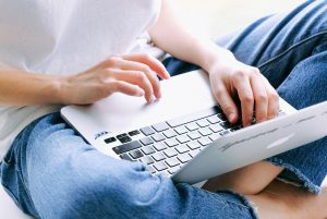 Woman with laptop in her lap, looking at screen   LMS Has a New Website